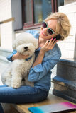 Cute blonde with Bichon Frise white dog Stock Photos