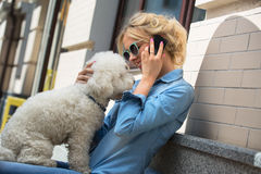 Cute blonde with Bichon Frise white dog. Cute blonde in sunglasses and a bright blue denim shirt emotionally talking on a cell phone. Bichon Frise white dog Stock Image