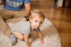 Cute blonde and blue-eyed baby dressed in a grey romper. Sitting on the carpet with father stock images