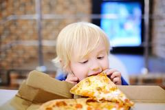 Cute blonde boy eating slice of pizza at fast food restaurant. Child unhealthy meal concept. Hungry kid. Pizza recipe stock images