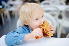 Cute blonde boy eating slice of pizza at fast food restaurant. Child unhealthy meal concept. Hungry kid. Pizza recipe stock image