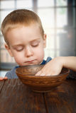 Cute blonde boy eats with hands stock photo