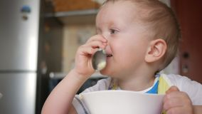 A cute blonde boy eats a porridge with a spoon from a plate of the house. Close-up stock video