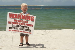 Cute Blonde Boy Happy The Beach Has Been Cleaned A. Blond boy holding up sign on beach in pensacola, standing in white sand with beautiful blue ocean water Stock Photos