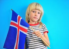 Cute blonde boy holding flag of Iceland royalty free stock image