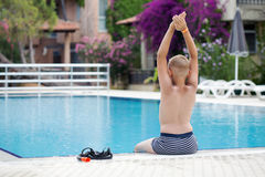 A cute blonde boy learning to dive. In a swimming pool stock photos