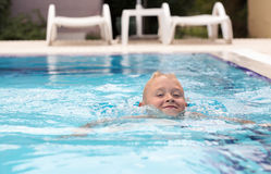 A cute blonde boy learning to swim stock image