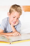 Cute blonde boy lying on bed reading a storybook Royalty Free Stock Photos