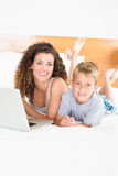Cute blonde boy and mother lying on bed using laptop Stock Photography