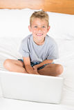 Cute blonde boy sitting on bed using laptop Royalty Free Stock Photography