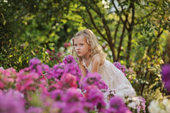 Cute blonde child girl in blooming summer garden. Cute blonde child girl in white dress playing in blooming summer garden Stock Image