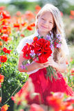 Cute blonde child girl with bouquet of poppies Royalty Free Stock Photo