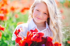 Cute blonde child girl with bouquet of poppies Stock Photos