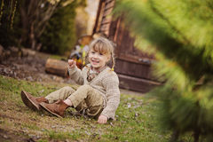 Cute blonde child girl having fun in early spring garden Stock Images