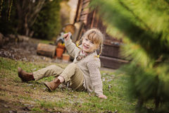 Cute blonde child girl having fun in early spring garden. Cute blonde child girl with pigtails hairstyle having fun in early spring garden Royalty Free Stock Images