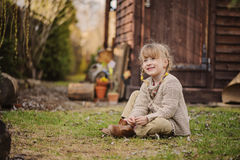 Cute blonde child girl having fun in early spring garden Stock Image