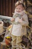 Cute blonde child girl having fun in early spring garden. Cute blonde child girl with pigtails hairstyle holding frame in early spring garden with primrose on Royalty Free Stock Photos