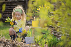 Cute blonde child girl having fun playing little gardener Royalty Free Stock Images