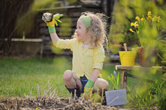 Cute blonde child girl having fun playing little gardener Royalty Free Stock Photo