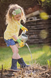 Cute blonde child girl having fun playing little gardener. Cute blonde child girl having fun watering plants in early spring garden Royalty Free Stock Photo