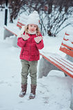 Cute blonde child girl looking at her hands on the walk in winter snowy park Royalty Free Stock Image