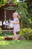 Cute blonde child girl plays toy wash in summer garden Royalty Free Stock Image