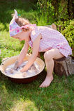 Cute blonde child girl plays toy wash in summer garden Royalty Free Stock Images
