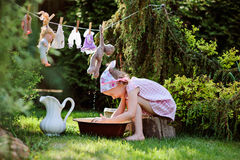 Cute blonde child girl plays toy wash in summer garden Stock Photography