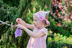 Cute blonde child girl plays toy wash in summer garden Stock Image
