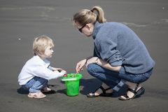 Cute Blonde Child and Her Mother Playing at the Beach Royalty Free Stock Photos