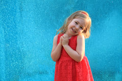 Cute blonde child praying on blue background Stock Photos