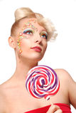 Cute blonde doll style model with candy Stock Photography