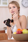 Cute blonde eating red grapes in kitchen. A cute blonde eating red grapes in kitchen Royalty Free Stock Photos