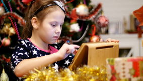 Cute blonde girl in a beautiful dress is printing a letter to Santa on a tablet, near presents and a Christmas tree. Decorated with beautiful Christmas lights stock video