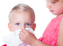 Cute blonde girl blowing her nose Royalty Free Stock Photos