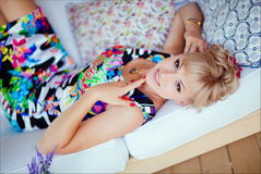 Cute blonde girl in a bright dress lying on a white sofa.  Royalty Free Stock Image