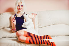 Cute blonde girl with candy and rabbit toy. Sitting on sofa Royalty Free Stock Photo