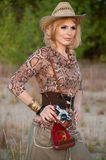 Cute blonde girl in a cowboy hat. Cute blonde girl in a cowboy hat and a camera in his hands Royalty Free Stock Images