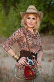 Cute blonde girl in a cowboy hat and camera Royalty Free Stock Photo
