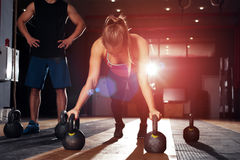 Cute blonde girl doing push ups in gym. Group of adults doing exercises with kettle bells. Cute blonde girl doing push ups in gym. Fitness, sports concept Royalty Free Stock Images
