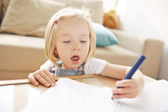 Cute Blonde Girl Drawing in Living Room Stock Photos