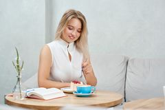 Cute blonde girl eating raspberry cake sitting in cafe. stock photos