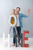 Cute blonde girl holding a huge letter O. With my father. Cute pretty blonde girl standing on the wooden decorations and holding a huge letter O while being with Royalty Free Stock Image