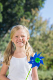 Cute blonde girl holding pinwheel smiling at camera Royalty Free Stock Images
