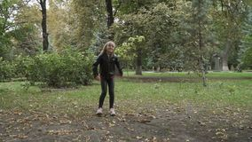 Cute blonde girl jumps in the park and send air kiss to camera stock video footage