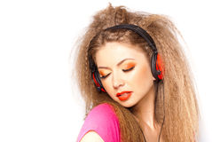 Cute blonde girl listening music on big headphones Stock Images