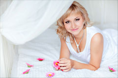 Cute blonde girl lying on a white bed, surrounded by small flowe Royalty Free Stock Images