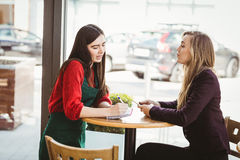 Cute blonde girl ordering from her friend. In a coffee shop Royalty Free Stock Photos