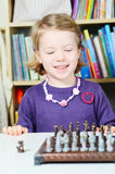 Cute, blonde girl playing chess Royalty Free Stock Photos