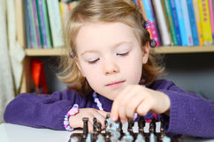Cute, blonde girl playing chess Stock Photos